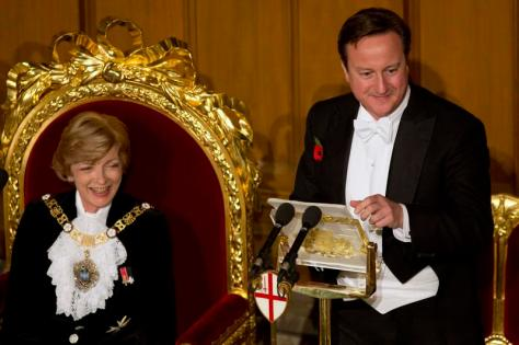 Lord Mayor of London Fiona Woolf (L) reacts as Britain's Prime Minister David Cameron delivers a speech at the Lord Mayor's Banquet at the Guildhall in the City of London November 11, 2013. REUTERS/Neil Hall (BRITAIN - Tags: POLITICS)